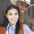 Young couple in cowboy outfits smiling for the camera — Stock Photo