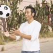 Stock Photo: Young man playing with a soccer ball