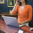 Businesswoman talking on cell phone with laptop — Zdjęcie stockowe