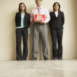 Businesspeople holding a help wanted sign — Stock Photo