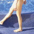 Close up of woman's legs walking next to pool — Stock Photo #13233089