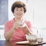 Senior Asian woman having tea — Stock Photo
