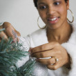 African woman putting ornament on Christmas tree — Stock Photo