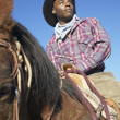 Young man in a cowboy outfit riding a horse — Stock Photo