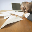 Businessman sleeping with paper airplanes on desk — Stock Photo