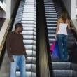 Africmlooking at womon escalator — Stok Fotoğraf #13233134
