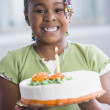 Stock Photo: African American girl holding birthday cake