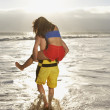 Rear view of man giving woman piggy back ride in ocean — Stock Photo