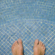 Man s bare feet in swimming pool - Stock Photo