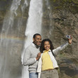 Couple taking own photograph with waterfall — 图库照片