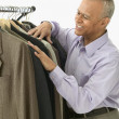 Businessman choosing a suit jacket - Stock Photo