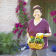 Portrait of woman with basket of flowers — Stok fotoğraf