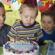 Boy blowing out birthday candles — Stock Photo