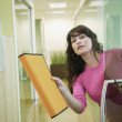Businesswoman holding out an orange folder — Stock Photo