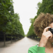 African woman taking photograph in park — Stock Photo