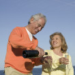 Husband and wife celebrating by the shore - Stock Photo