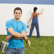Multi-ethnic couple painting fence — Foto de Stock