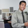 Portrait of Asian businessman holding cell phone — Stock Photo