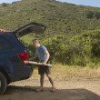 Stock Photo: Man packing surfboard into SUV