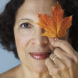 Senior African woman holding autumn leaf over eye - Stock Photo