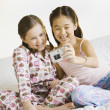 Stock Photo: Two girls taking own photograph on bed