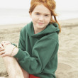 Girl with freckles sitting on beach — Stock Photo