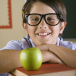 Hispanic boy with stack of books and apple in classroom — Stock Photo #13233396