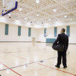 Asian businessman on empty basketball court — Stock Photo
