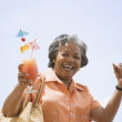 Portrait of senior African woman holding tropical cocktail - 图库照片
