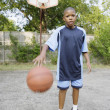 Young boy dribbling basketball — Stock Photo #13233453