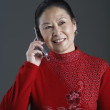 Senior Asian woman talking on cell phone — Stock Photo