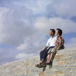 Asian couple sitting on a wall — Stock Photo