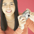Royalty-Free Stock Photo: Young woman holding a camera