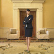 Businesswoman standing in waiting area - Stock Photo