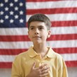 Boy in front of American flag with hand over heart — Stock Photo #13233503