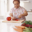Senior Hispanic woman chopping vegetables - Stock Photo