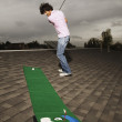 Young man playing miniature golf on roof - Stock Photo