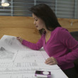 Businesswoman examining blueprints - Stock Photo