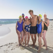 Group of senior women in bathing suits with young man at beach — Stock Photo