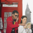 Asian couple using public telephone box and map in London - Stock Photo