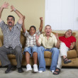 Multi-generational Hispanic male family members cheering on sofa - Stock Photo