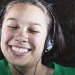 Portrait of a teenage girl wearing headphones smiling — Stock Photo
