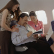 Mature man getting female attention on airplane - Stock Photo