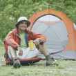 Stock Photo: Young mat his campsite