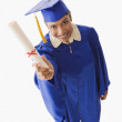 Stock Photo: High angle view of Indian woman in graduation cap and gown holding diploma