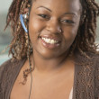Close up of African woman smiling and wearing headset — Stock Photo