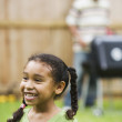 African girl with father barbequing in background — Stock Photo