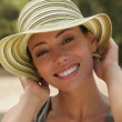 Foto Stock: Young woman smiling in sunhat