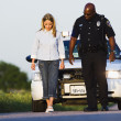 Foto Stock: Policeman watching young woman walk in a straight line