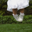 Hispanic girl jumping on grass — Stock Photo